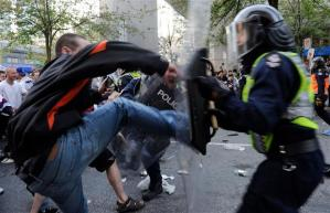 Blue jean's clad thug kicks the shield of the riot police.